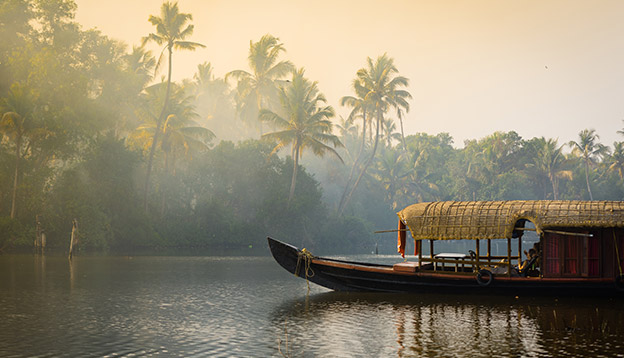 A traditional house boat is anchored on the shores of a fishing lake in Kerala's Backwaters, India. Photo Credit: Shutterstock.