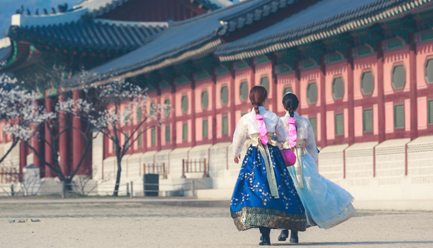 Korean Girls dressed Hanbok in traditional dress walking in Gyeongbokgung Palace, Seoul, South Korea. Photo Credit: Shutterstock.