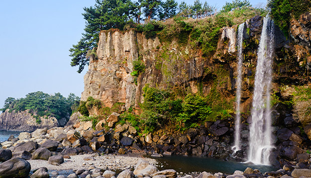 view of famous Jeongbang Waterfall on Jeju Island of South Korea. Photo Credit: Shutterstock.