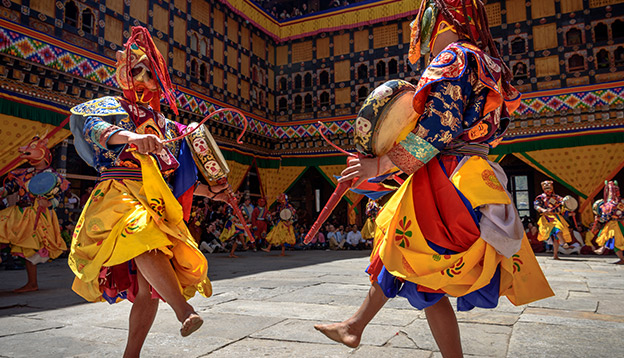 2 Monks dancing for colorful mask dance at yearly Paro Tsechu festival in Bhutan. Photo Credit: Shutterstock