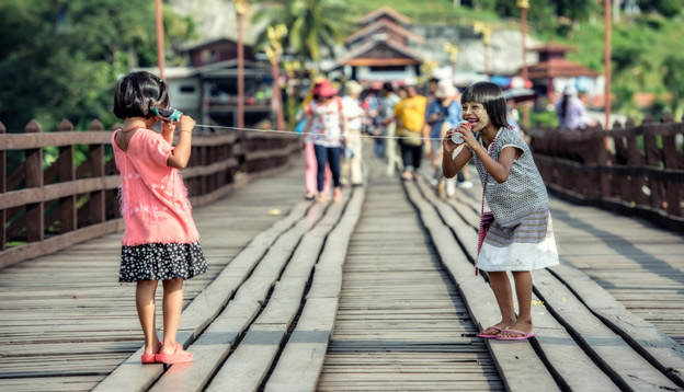 Girls playing with cable phone, Myanmar. Photo Credit: Shutterstock