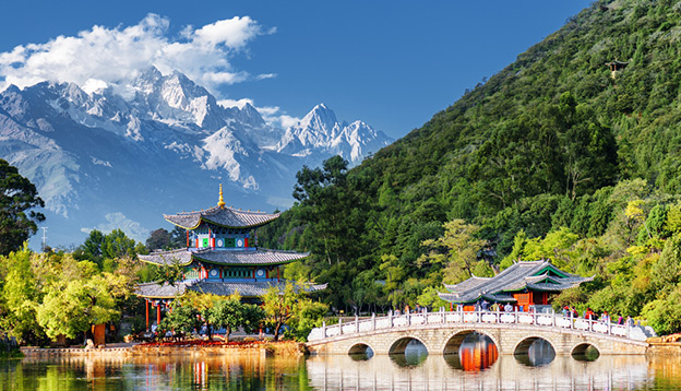 Amazing view of the Jade Dragon Snow Mountain and the Black Dragon Pool, Lijiang, Yunnan province, China. The Suocui Bridge over pond and the Moon Embracing Pavilion in the Jade Spring Park. Photo Credit: Shutterstock