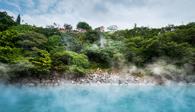 Blue hot spring pond in forest of Xinbeitou thermal valley, Taiwan. Photo Credit: Shutterstock